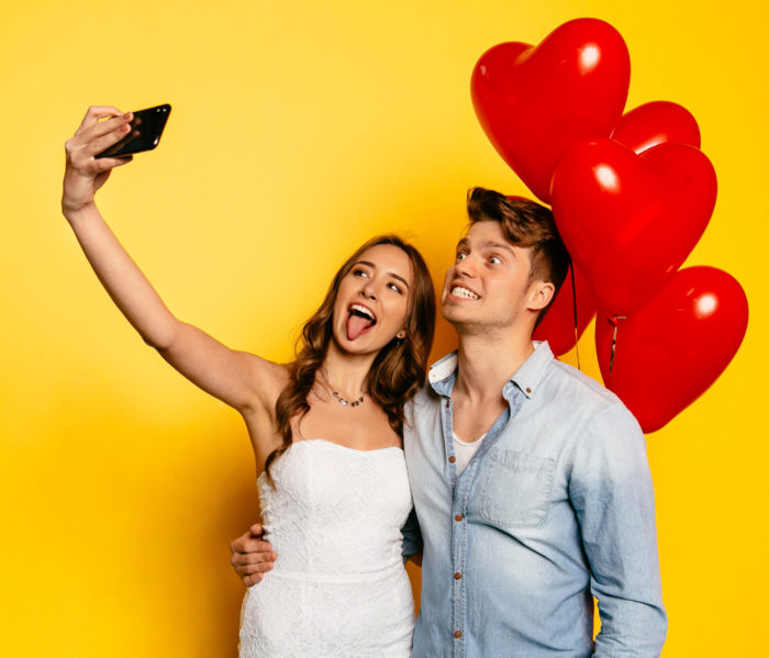 Beautiful girl showing a tongue standing with boyfriend showing teeth taking selfie, with balloons. Celebrating St. Valentine's day.